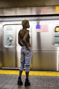 USA, New York City, woman waiting on subway station platform - MAUF01230
