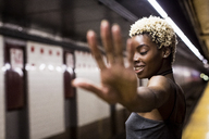 USA, New York City, portrait of laughing woman on subway station platform raising hand - MAUF01233