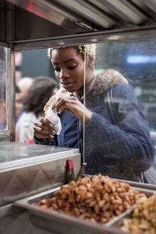 Portrait of young woman buying food on stall - MAUF01236