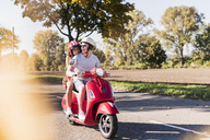 Happy young couple riding motor scooter on country road - UUF12260