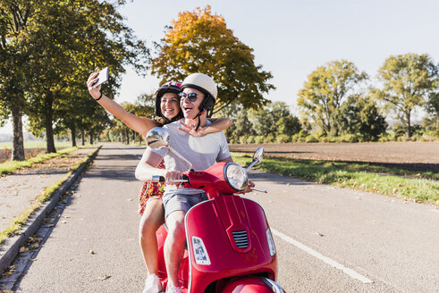 Happy young couple taking a selfie on motor scooter on country road - UUF12269