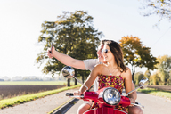Happy young couple taking a selfie on motor scooter on country road - UUF12272