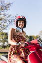 Portrait of happy young woman on motor scooter - UUF12275