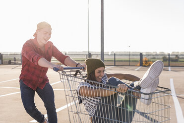 Playful young couple with shopping cart on parking level - UUF12296