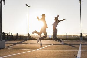 Carefree young couple jumping on parking levelat sunset - UUF12302
