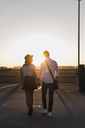 Young couple walking hand in hand on parking level at sunset - UUF12308