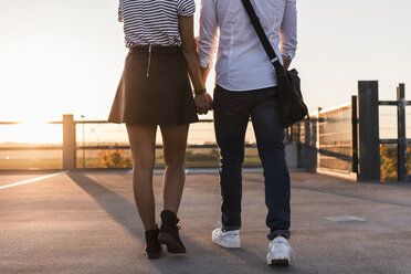 Young couple walking hand in hand on parking level at sunset - UUF12311