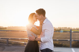 Young couple kissing on parking level at sunset - UUF12314
