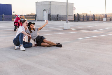 Happy young couple with motor scooter on parking level taking a selfie - UUF12317