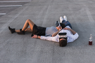 Young couple lying on parking level wearing VR glasses - UUF12320
