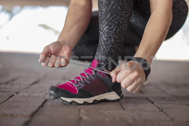 Sportive woman tying her shoes - ZEF14825