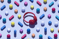 Red wireless headphones surrounded by geometric shapes, 3D Rendering - DRBF00039