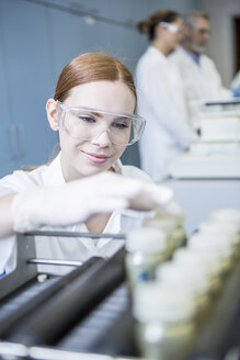 Smiling scientist in lab with samples - WESTF23692
