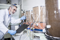 Scientist with clipboard working in lab - WESTF23698