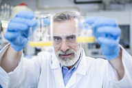 Scientist in lab holding up two beakers with liquid - WESTF23704