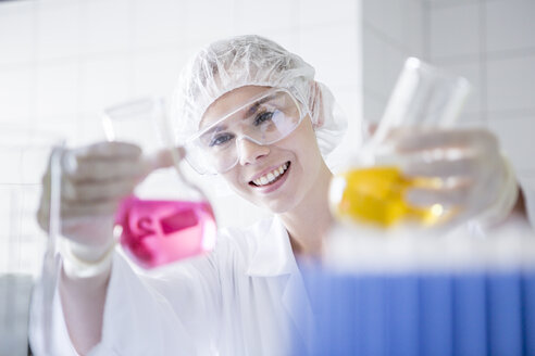 Smiling scientist in lab holding up two beakers with liquids - WESTF23734