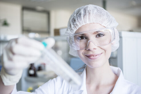 Portrait of smiling scientist in lab holding test tube - WESTF23737