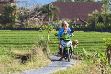 Woman with child and dog riding motor scooter on country lane - KNTF00921