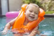 Portrait of happy boy wearing life jacket in swimming pool - KNTF00930