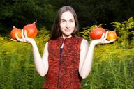 Portrait of smiling woman in the garden holding four organic Hokkaido pumpkins - NDF00687