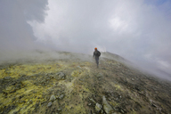 Italy, Sicily, Mount Etna summit, young man hiking on sulfur field - THGF00027