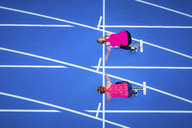 Top view of two female runners starting on tartan track - STSF01425