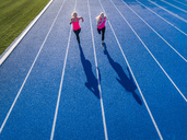 Aerial view of two female runners on tartan track - STSF01428