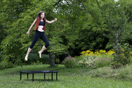 Woman jumping on trampoline in the garden - NDF00696