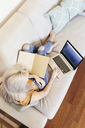 Young woman with notebook and laptop on couch at home - GIOF03351