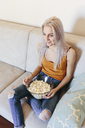 Smiling young woman sitting on couch at home with bowl of popcorn - GIOF03354