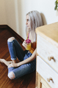 Serious young woman sitting on the floor at home - GIOF03360