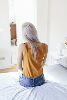 Rear view of young woman with long blond hair sitting on bed at home - GIOF03366