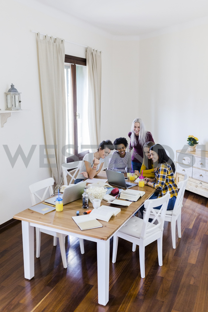 Group of female students sharing laptop at table at home - GIOF03387 - Giorgio Fochesato/Westend61