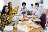 Group of young women at home studying and having pizza - GIOF03393