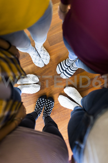 Close-up of feet of five women standing on wooden floor - GIOF03417