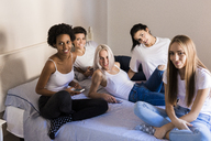 Portrait of female friends with cell phones in bedroom - GIOF03429