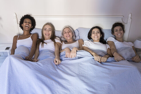 Portrait of happy female friends lying in bed side by side - GIOF03435
