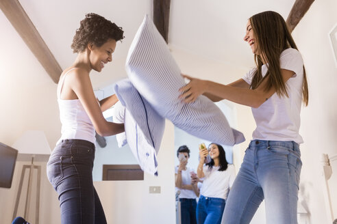 Playful female friends having a pillow fight in bed - GIOF03444