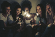 Happy female friends with sparklers in the dark - GIOF03453
