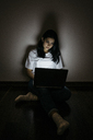 Young woman at home sitting on floor using laptop in the dark - GIOF03456
