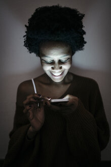 Smiling young woman using cell phone in the dark - GIOF03459