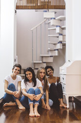 Portrait of smiling female friends sitting on the floor at home - GIOF03465