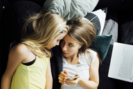 Relaxed mother and daughter with cell phone on sofa - JPF00284