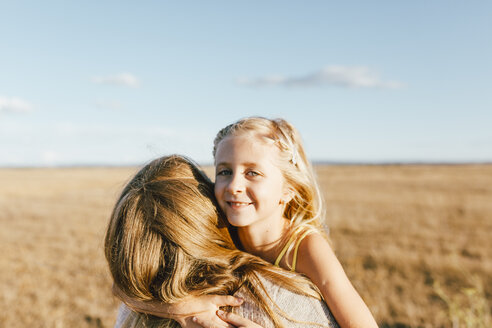 Portrait of smiling daughter hugging mother at a field - JPF00287