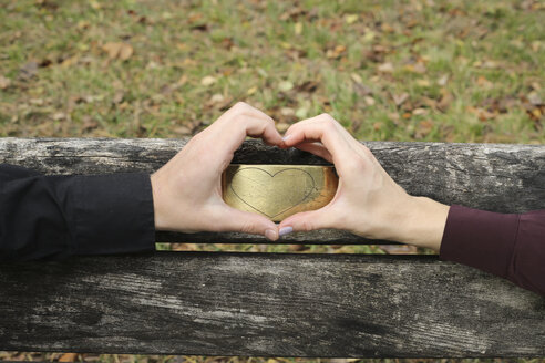 Hands of a couple shaping a heart on a bench - FCF01314