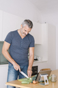 Mature man in kitchen cutting vegetables and looking at tablet - ALBF00251