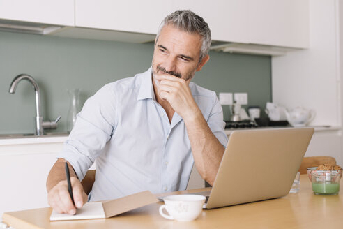 Smiling man writing in notebook and using laptop in home office - ALBF00254