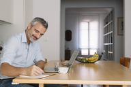 Smiling man writing in notebook and using laptop in home office - ALBF00257