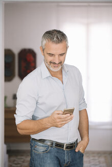 Smiling mature man using cell phone at home - ALBF00263
