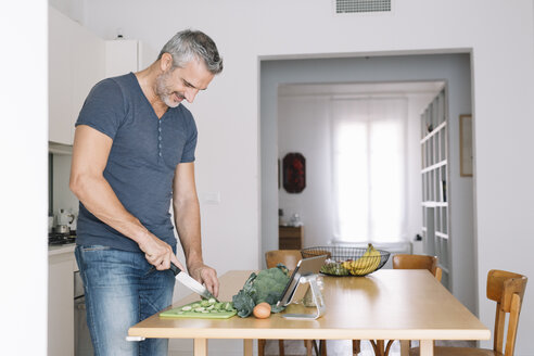 Mature man in kitchen cutting vegetables and looking at tablet - ALBF00266